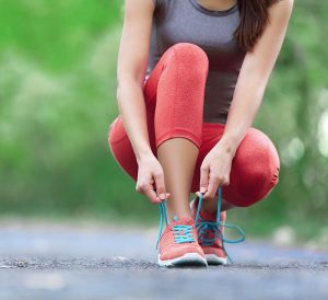 Woman kneeling down on a running path tying her running shoes
